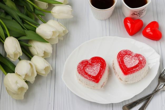 Gâteaux à la gelée en forme de coeur, café et tulipes sur une surface blanche