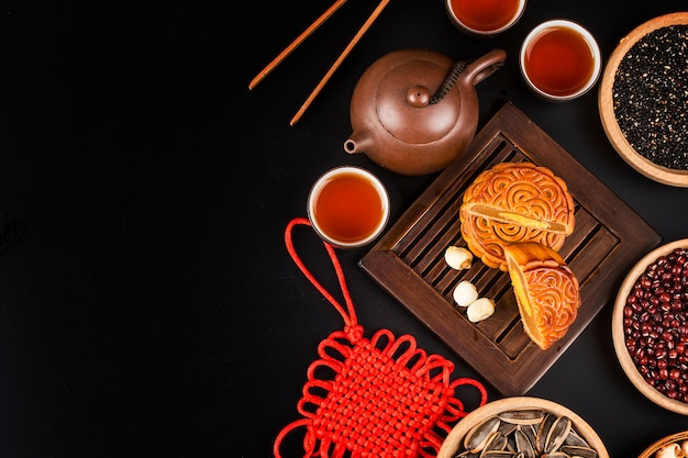 Gâteaux de lune traditionnels sur le réglage de la table avec une tasse de thé.