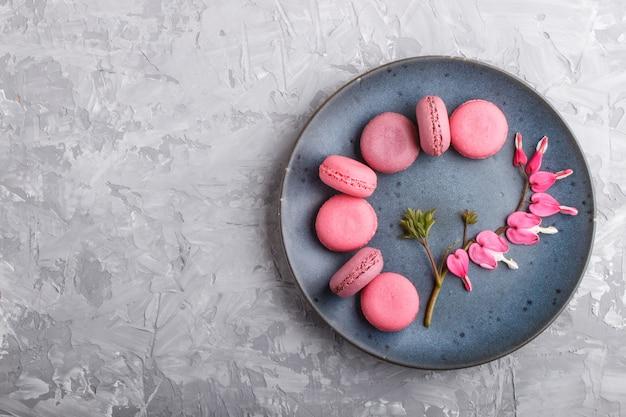 Gâteaux macaron ou macaron pourpres et roses sur plaque de céramique bleue sur béton gris