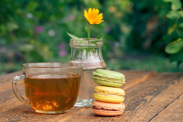 Gâteaux de macarons de couleur différente, fleur de calendula avec une tige dans un bocal en verre et tasse de thé vert
