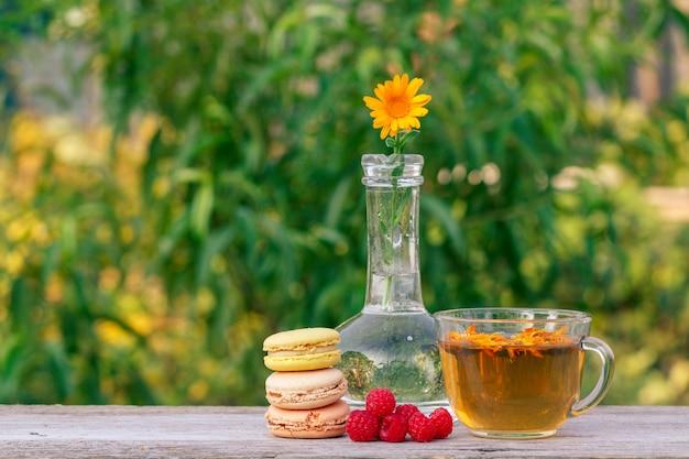 Gâteaux de macarons de différentes couleurs, fleur de calendula dans un flacon en verre et tasse de thé vert.