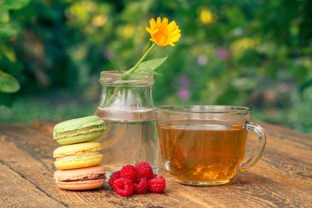 Gâteaux de macarons, fleur de calendula avec une tige dans un bocal en verre, framboises fraîches et tasse de thé vert