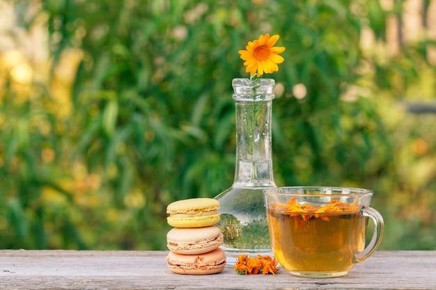 Gâteaux de macarons, fleur de calendula avec une tige dans un flacon en verre et tasse de thé vert.