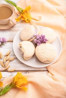 Gâteaux de meringue avec tasse de café sur un fond en bois blanc et textile en lin orange. vue de côté,