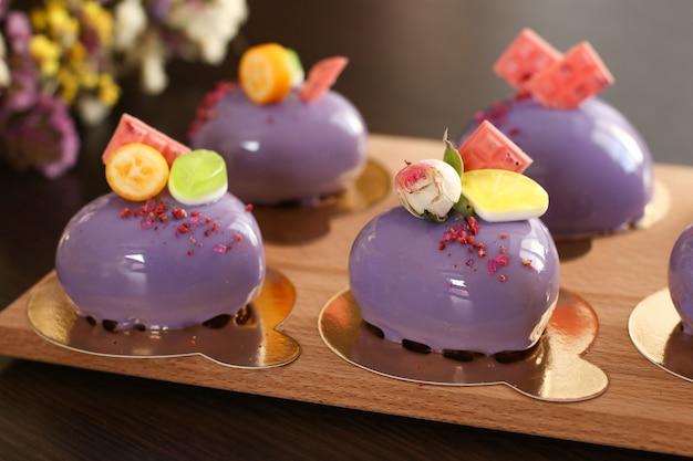 Gâteaux de mousse brillants faits maison coeurs avec glaçage miroir violet sur un fond sombre