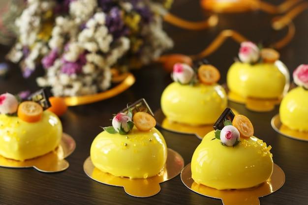 Gâteaux mousse lumineux faits maison coeurs avec revêtement miroir jaune sur fond sombre