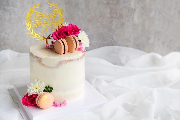 Gâteaux nus mignons décorés de macaron et de fleur rose sur fond de tissu blanc. concept de gâteau et de boulangerie moderne