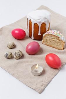 Gâteaux de pâques et oeufs colorés sur la table de fête de pâques avec une bougie allumée.