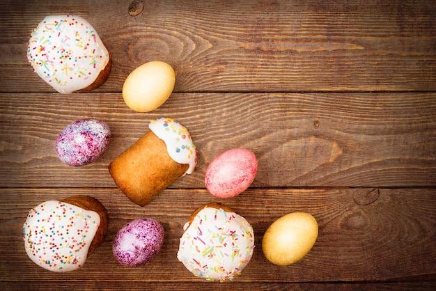 Gâteaux de pâques et oeufs de pâques colorés sur un fond en bois.