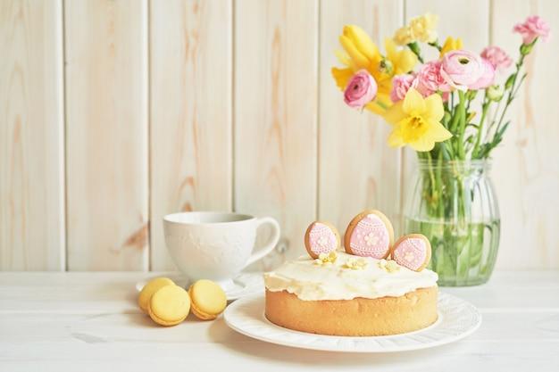 Gâteaux de pâques sur table, macarons, œufs et bouquet de fleurs à vaseaster