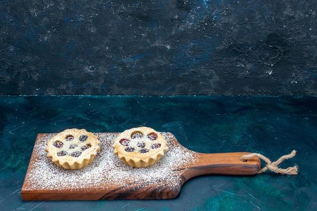 Gâteaux en poudre de sucre peu formés avec des fruits sur bleu foncé