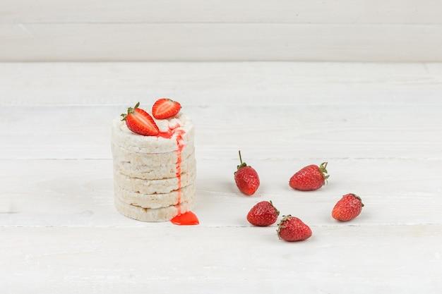 Gâteaux de riz blanc gros plan avec des fraises sur la surface de la planche de bois blanc. horizontal