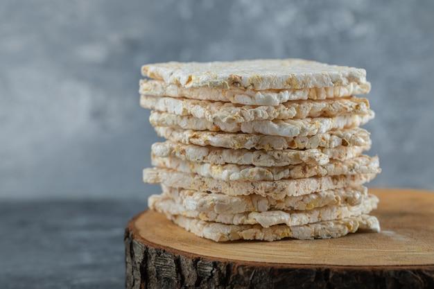 Gâteaux de riz secs en forme de carré sur un morceau de bois.