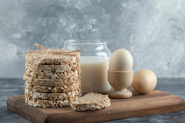Gâteaux de riz soufflé, lait et œufs sur planche de bois
