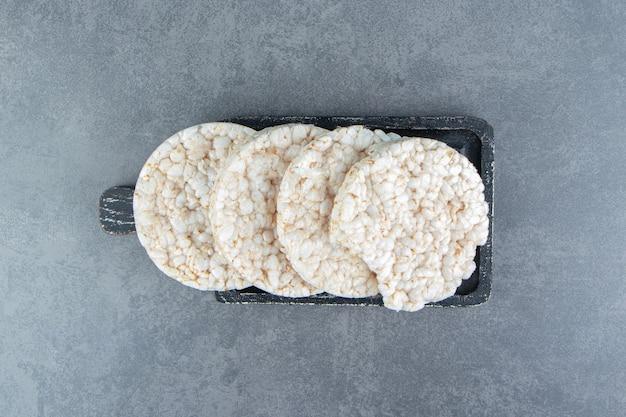 Gâteaux de riz soufflé sur une planche sombre en bois.