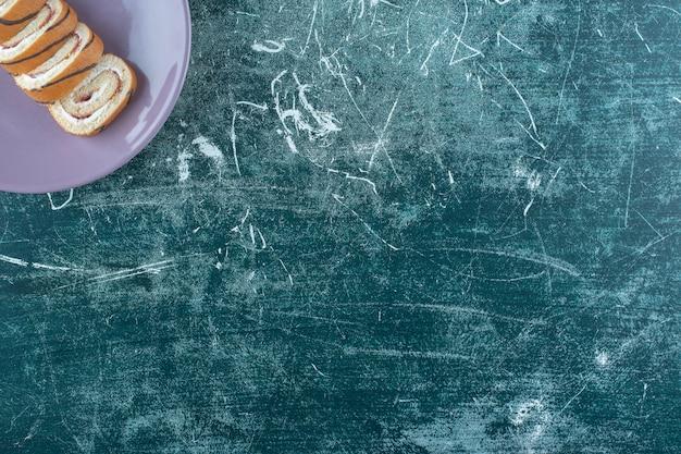 Gâteaux roulés en tranches sur une assiette, sur la table bleue.