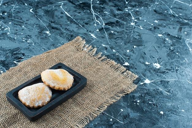 Gâteaux sucrés sur plaque de bois sur une texture , sur la table bleue.
