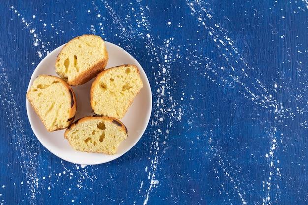 Gâteaux tranchés savoureux frais placés sur une assiette blanche