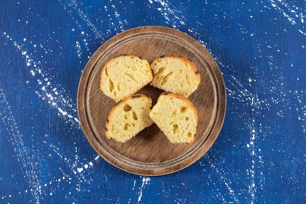 Gâteaux tranchés savoureux frais placés sur une assiette en bois