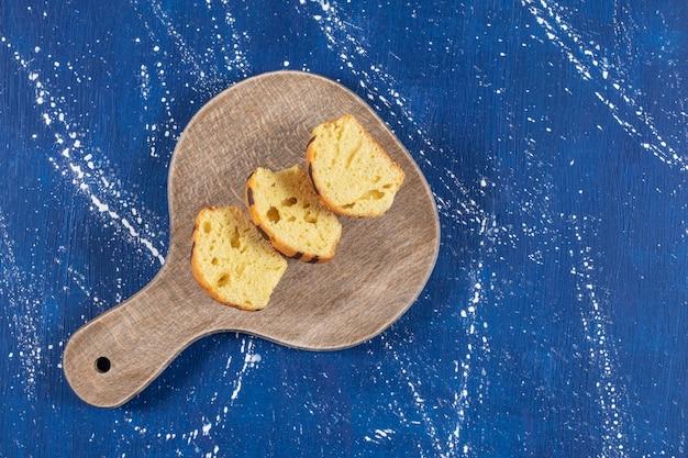Gâteaux tranchés savoureux frais placés sur une planche de bois