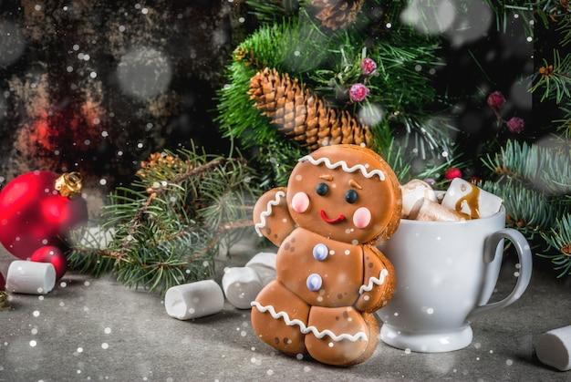 Gâterie de noël traditionnelle. chocolat chaud avec guimauve, biscuit de pain d'épice, branches de sapin et fond de décorations de noël