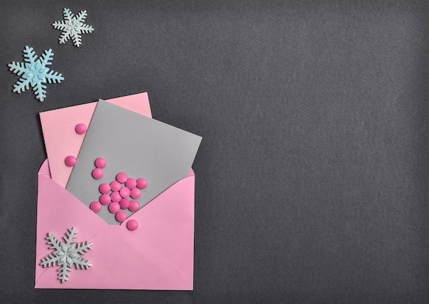A gauche sur fond noir, une enveloppe rose avec des cartes postales