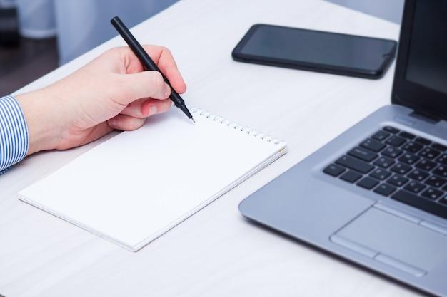 Un gaucher écrit dans un cahier. concept de jour de gauche.