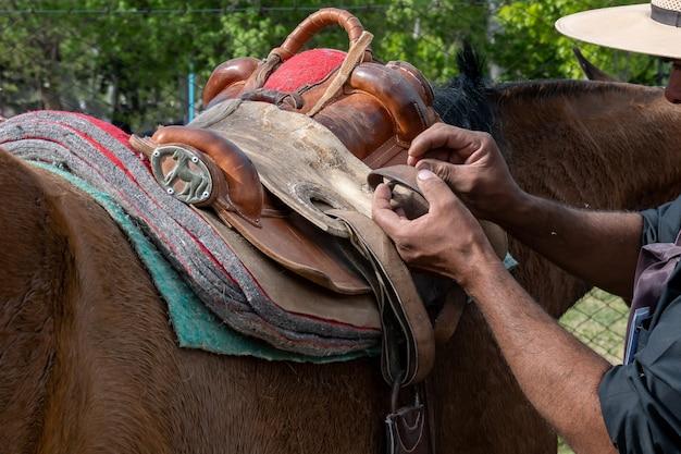 Gaucho argentin fixant la selle de cheval