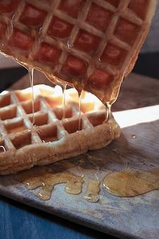 Gaufre au miel tombant sur une table en bois