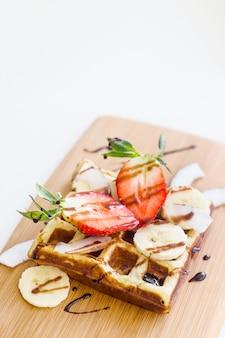 Gaufre belge avec fruits et sauce au chocolat est joliment servi sur une planche de bois