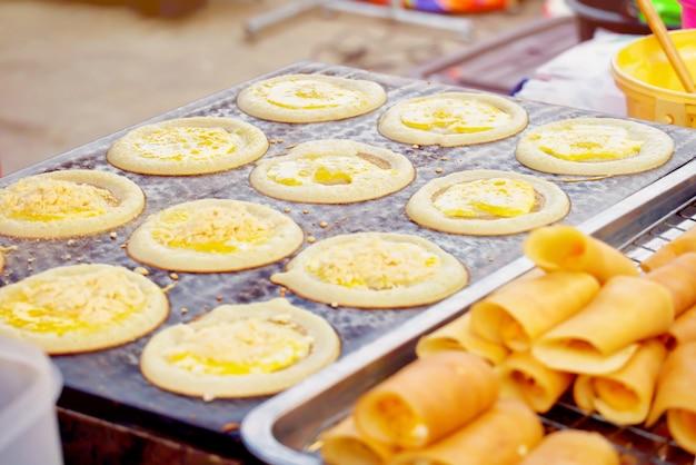 Gaufre douce à la crème ou roll pancake fourré à la crème sur le feu. dessert thaï au marché.