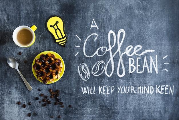 Gaufres au chocolat; tasse à café et ampoule à découper en papier avec texte sur tableau noir