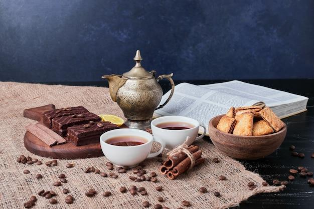 Gaufres au chocolat avec une tasse de thé et des craquelins.