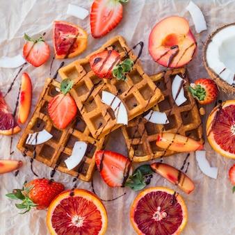 Gaufres aux fraises, noix de coco, prune et orange au chocolat