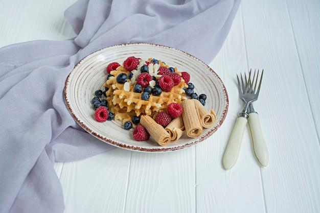 Gaufres aux fruits frais pour le petit déjeuner. gaufres ensoleillées. fond en bois blanc