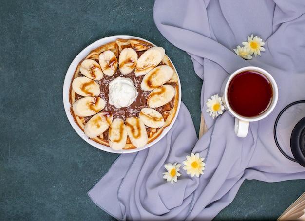 Gaufres à la banane tranchée, sauce au chocolat et crème glacée. vue de dessus.