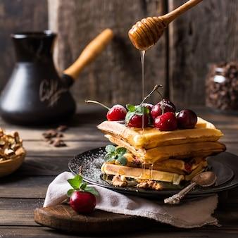 Gaufres belges au miel et au sucre en poudre. cerises. grains de café en pot. café turc