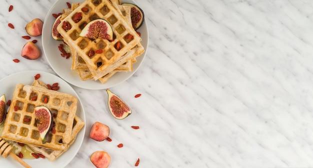 Des gaufres belges en bonne santé; figue; mon chéri; et louche de miel servis dans l'assiette contre le sol en marbre