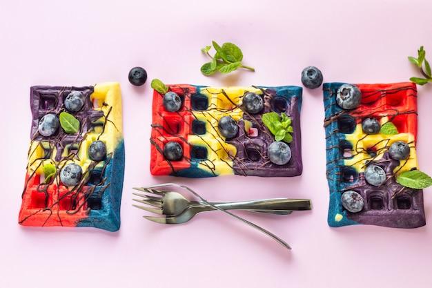 Gaufres belges colorées avec glaçage au chocolat, bleuets et menthe