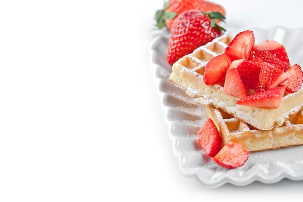 Gaufres belges avec du sucre en poudre et des fraises sur une plaque en céramique sur le tableau blanc.