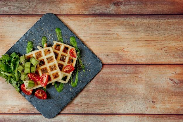Gaufres belges fraîchement cuites au four avec roquette, tomates et avocat sur une plaque noire. gaufres salées. concept de petit déjeuner. petit-déjeuner sain