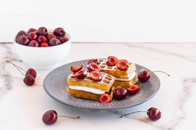Gaufres belges maison avec crème fouettée et cerises servies sur une assiette pour le petit-déjeuner.