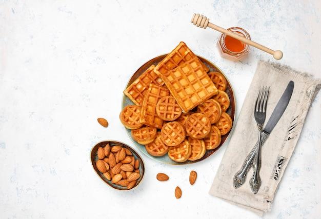 Gaufres belges traditionnelles avec des baies fraîches et du miel sur une surface en béton gris.