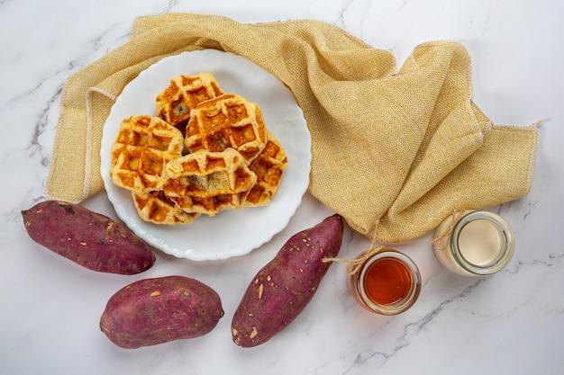 Gaufres belges traditionnelles, oranges sanguines et vinaigrette aux bleuets et tasse de café pour le petit déjeuner sucré, composition sur fond clair.