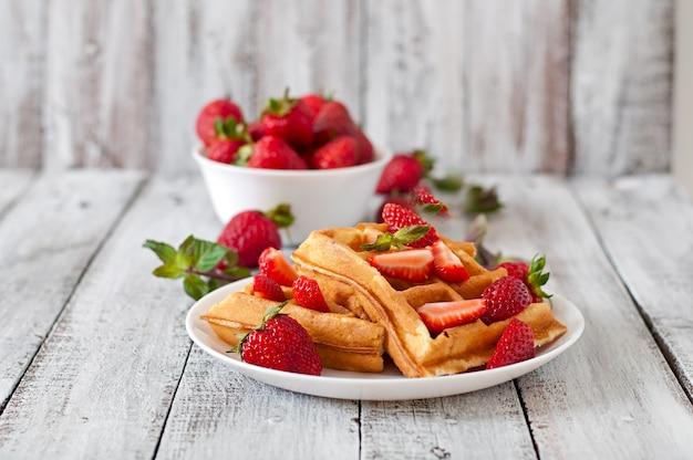 Gaufres de belgique aux fraises et menthe sur plaque blanche