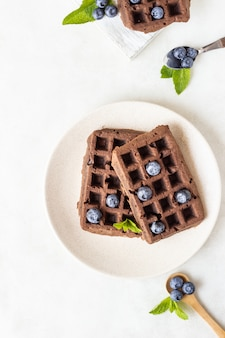 Gaufres bruxelloises au chocolat avec myrtilles et menthe sur une assiette.