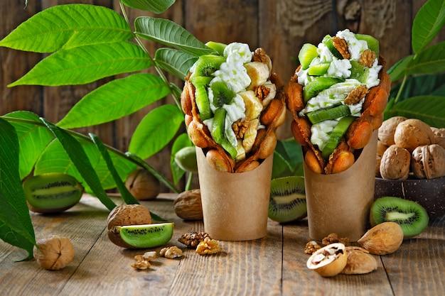 Gaufres à bulles de hong kong farcies de crème fouettée et de kiwis et de tranches de banane et de noix