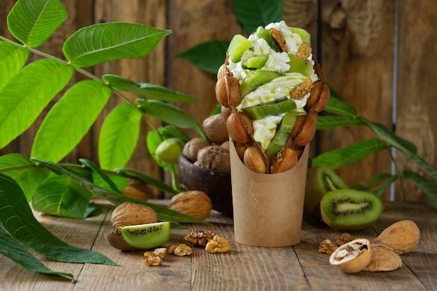Gaufres à bulles de hong kong farcies de crème fouettée et de tranches de kiwi et de noix