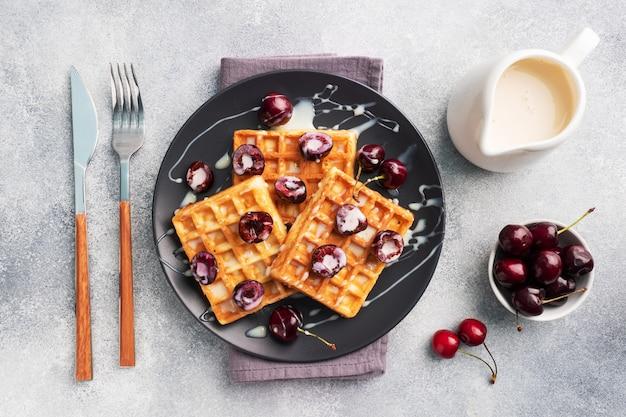 Gaufres cannelées belges avec cerises fraîches et crème sur une assiette. gaufres maison douces, dessert sucré aux cerises.