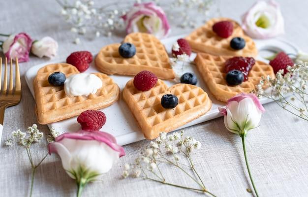 Gaufres coeur belge maison avec sauce aux fraises et baies avec fleurs